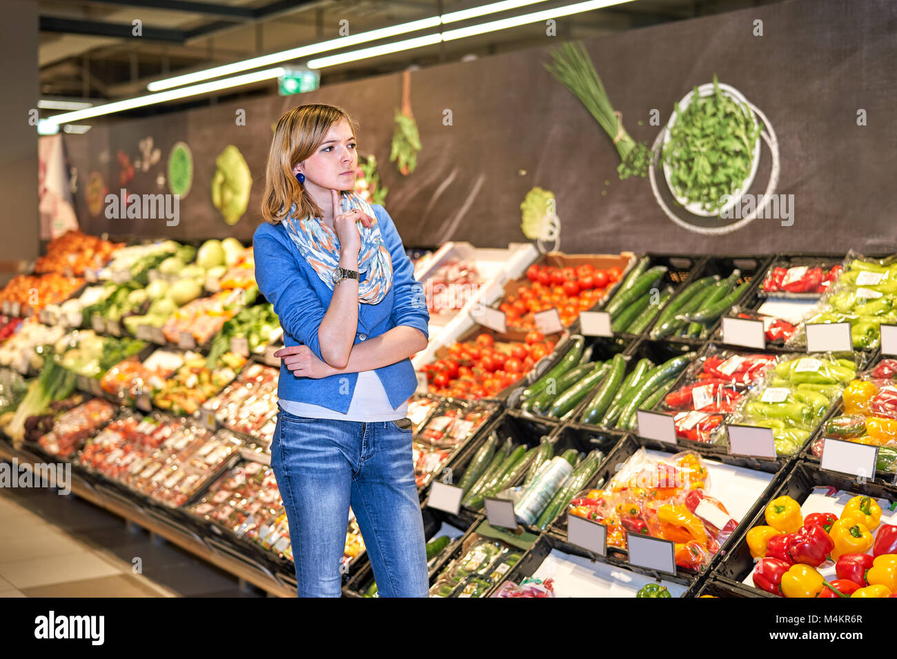 Young woman staying confused in grocery store - Stock Image