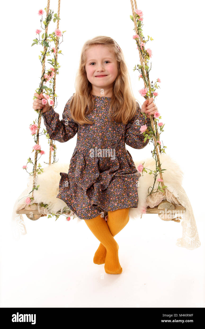 pretty little girl playing on decretive swing, happy and having fun, 4 year old girl - Stock Image