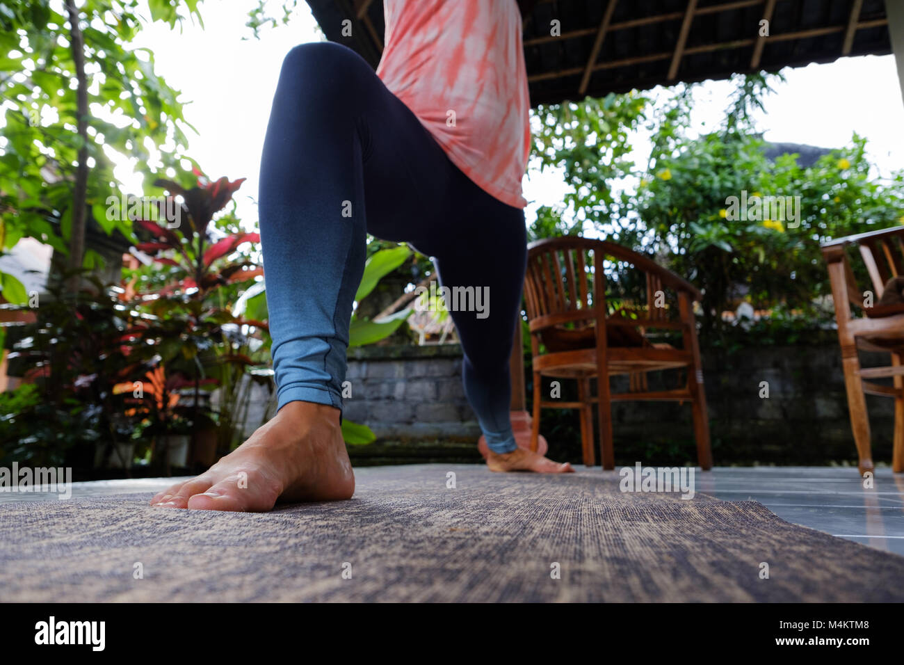 Young woman doing yoga asana Virabhadrasana Warrior Pose outside on terrace during vacation. - Stock Image