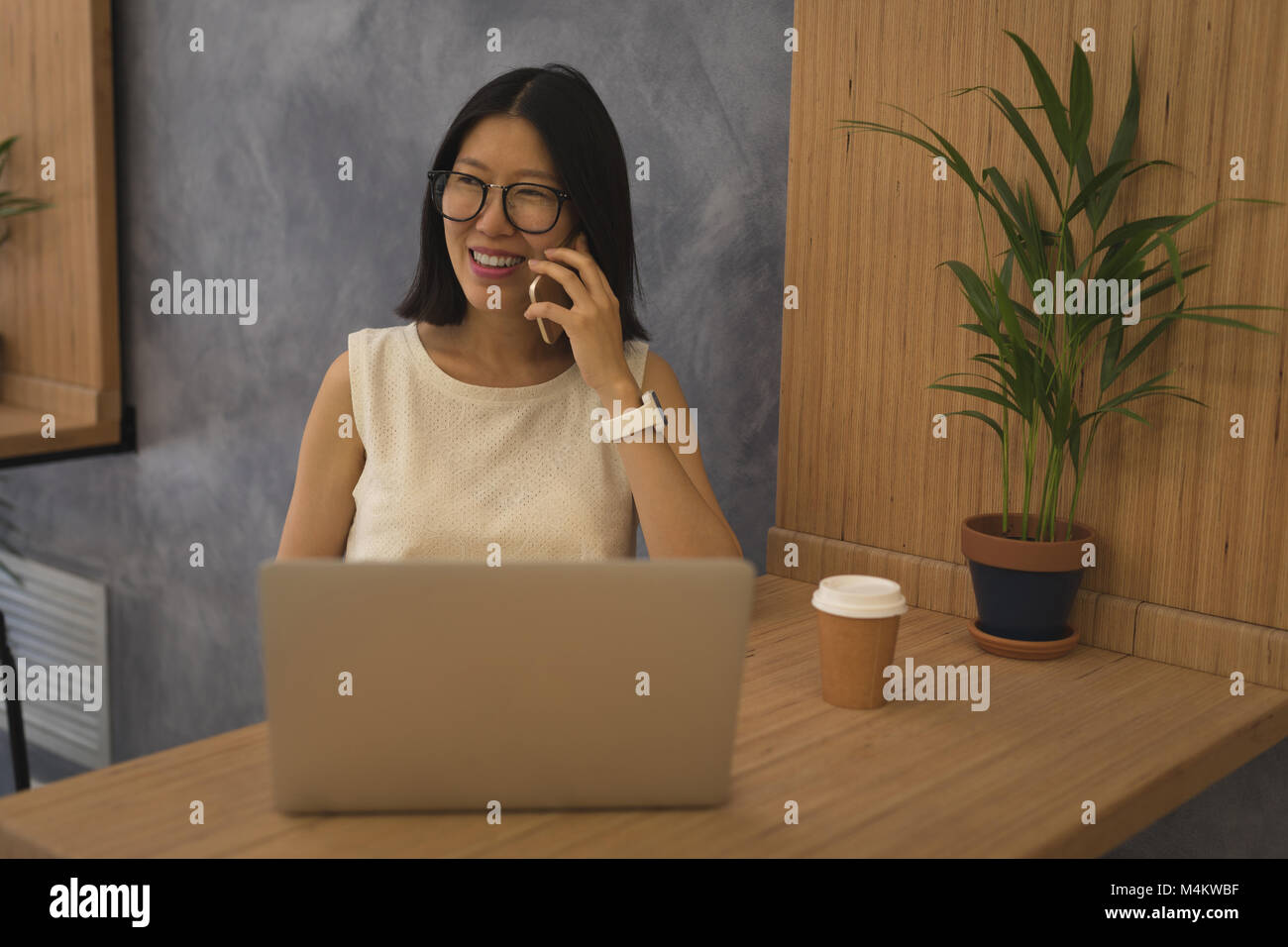 Pregnant businesswoman talking on mobile phone at desk Stock Photo