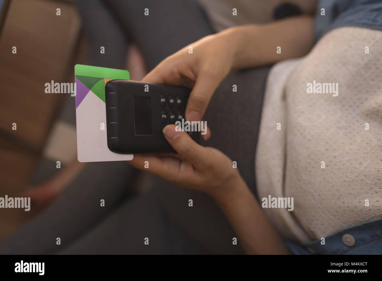 Pregnant woman making payment though bio metric system - Stock Image