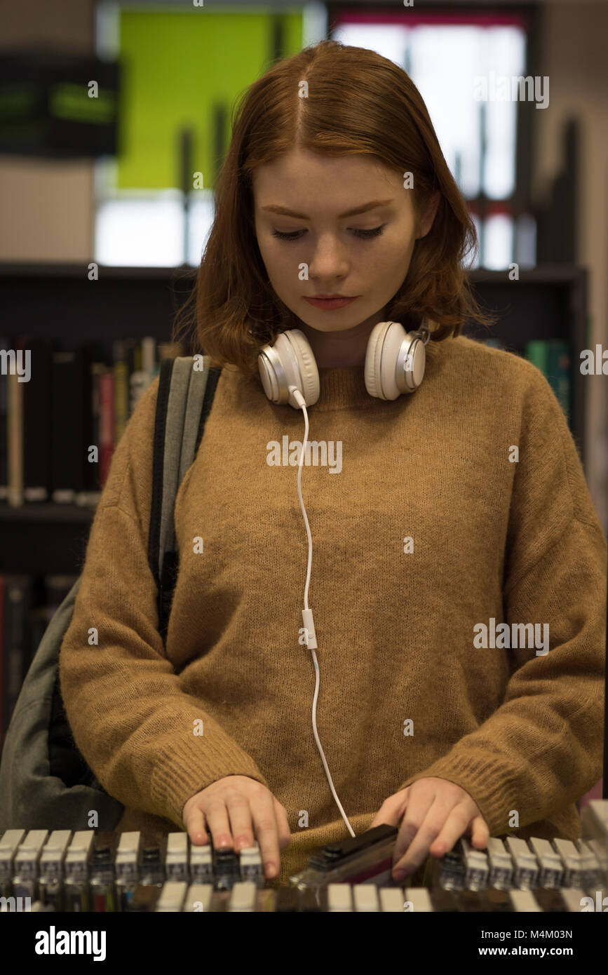 Young woman picking up cassette - Stock Image