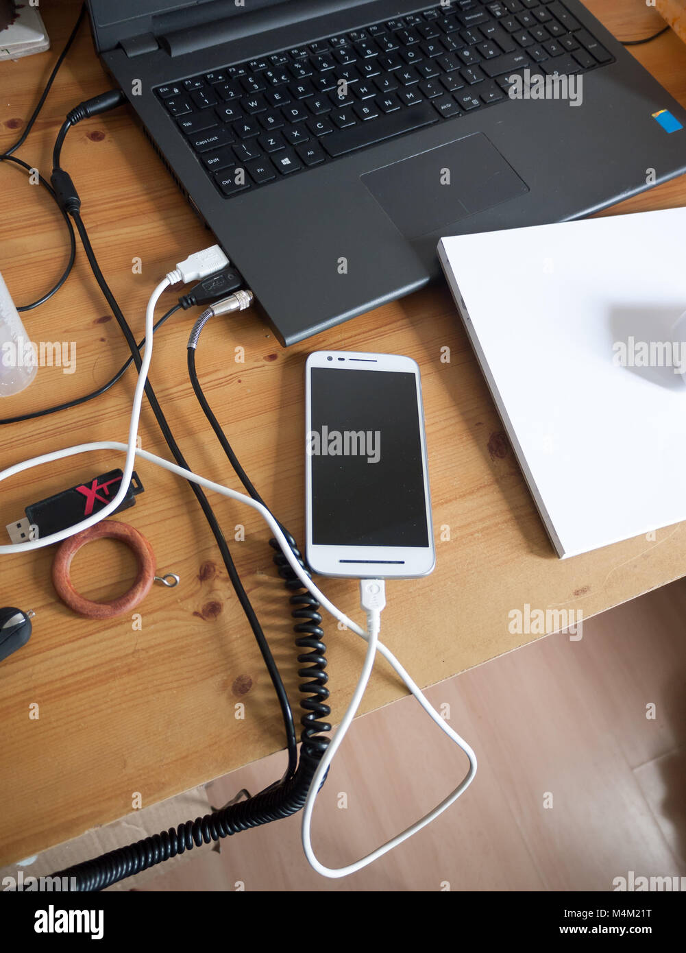 a messy student desk with laptop, phone and paper - Stock Image