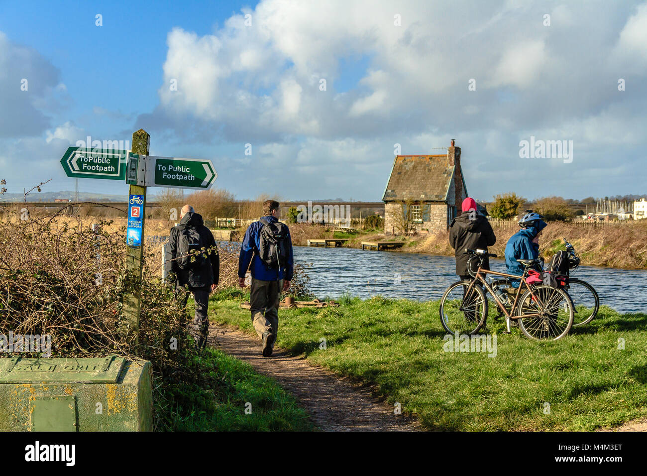 Cyclists and walkers by a canal on the Exe Estuary, near the ferry to Topsham. - Stock Image