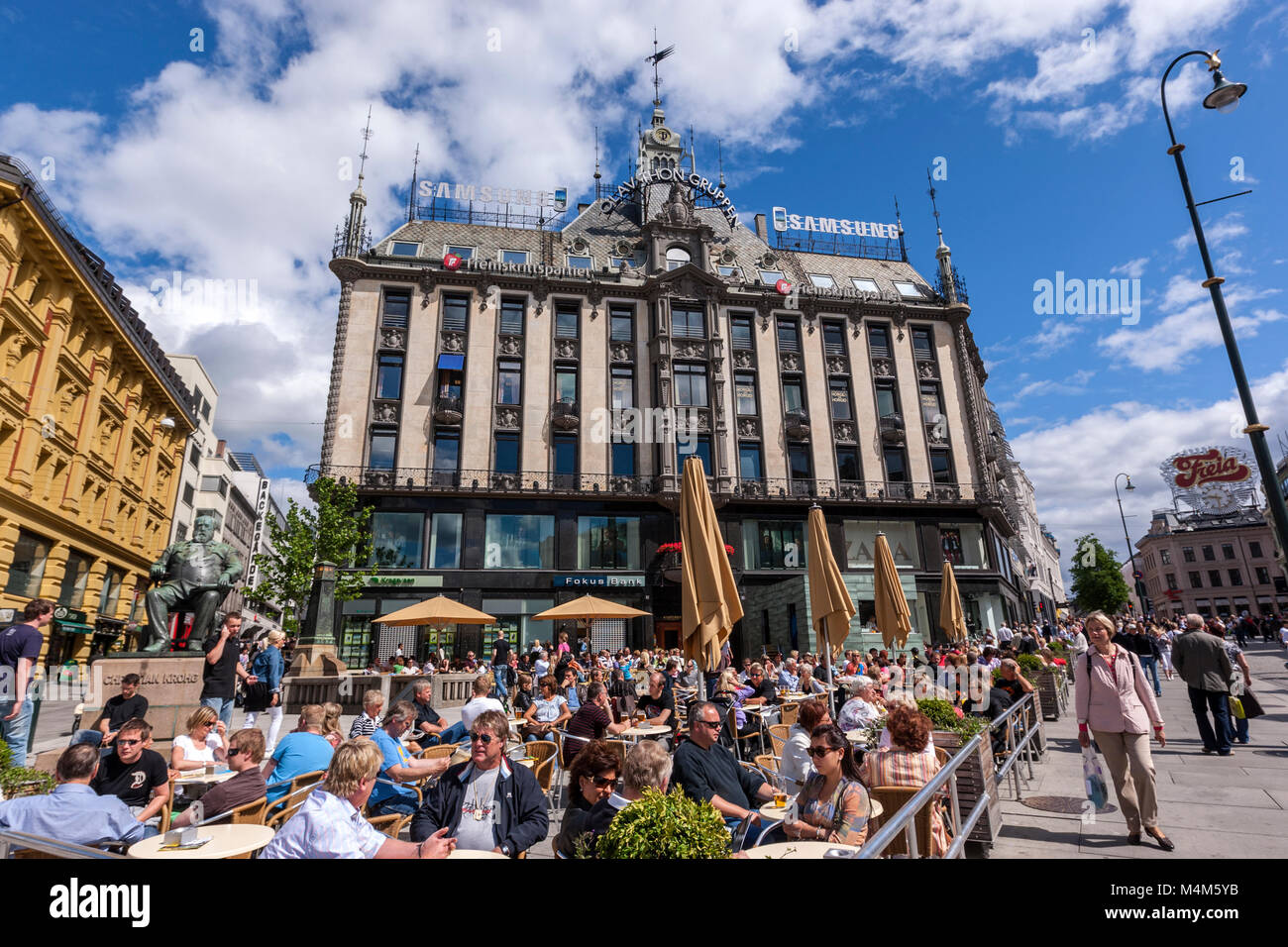 Sunny summer day with terrace full of people in front of Olav Thon Gruppen house, Karl Johans gate, Oslo, Norway - Stock Image