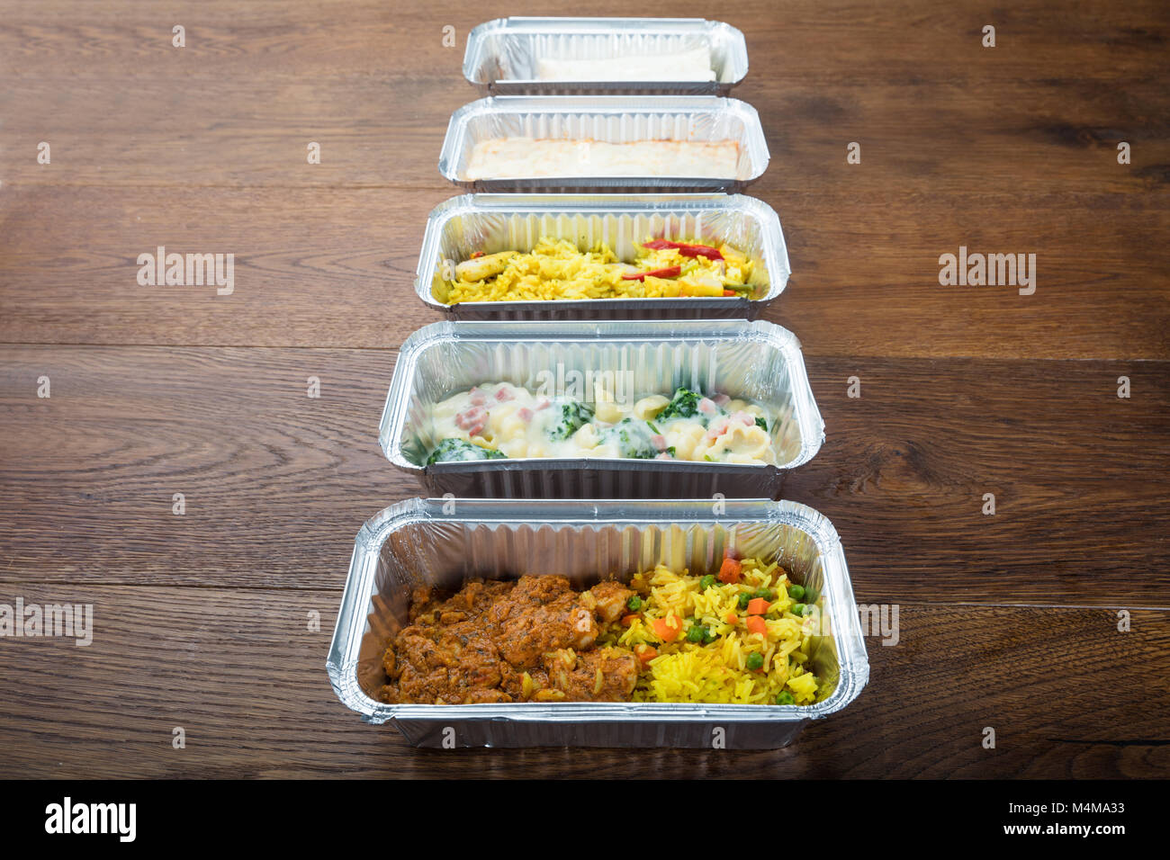 Row Of Take Away Dishes In Foil Container On Wooden Table Stock