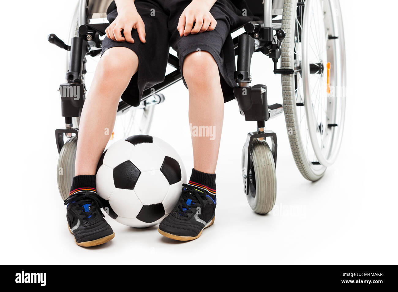 Disabled child boy sitting on wheelchair holding soccer ball - Stock Image