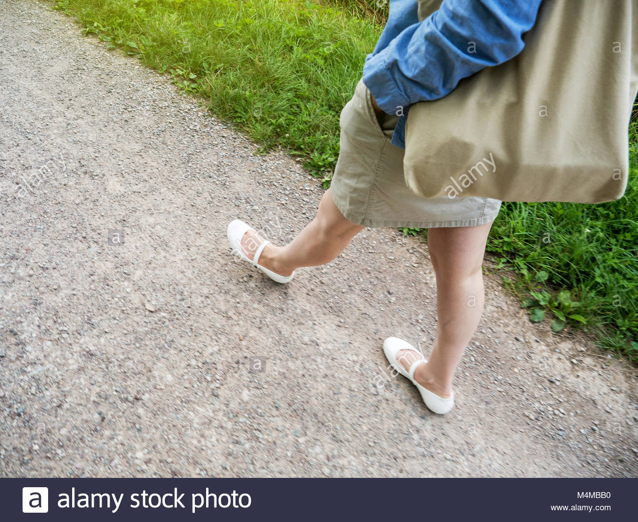Woman walking carefree on rural path - Stock Image