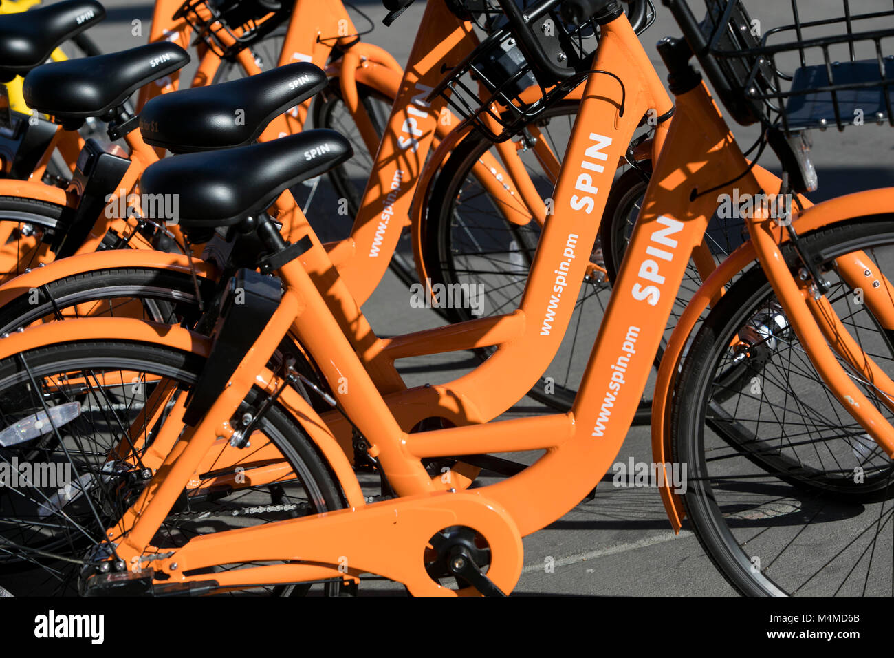 A row of Spin dock-less bicycle-sharing bikes in Tempe, Arizona, on February 3, 2018. - Stock Image