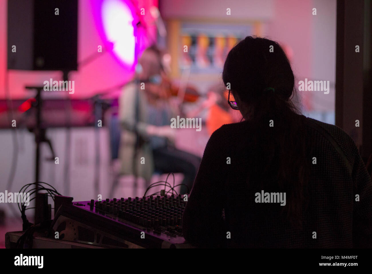 recording technicians at mixing desk during concert - Stock Image