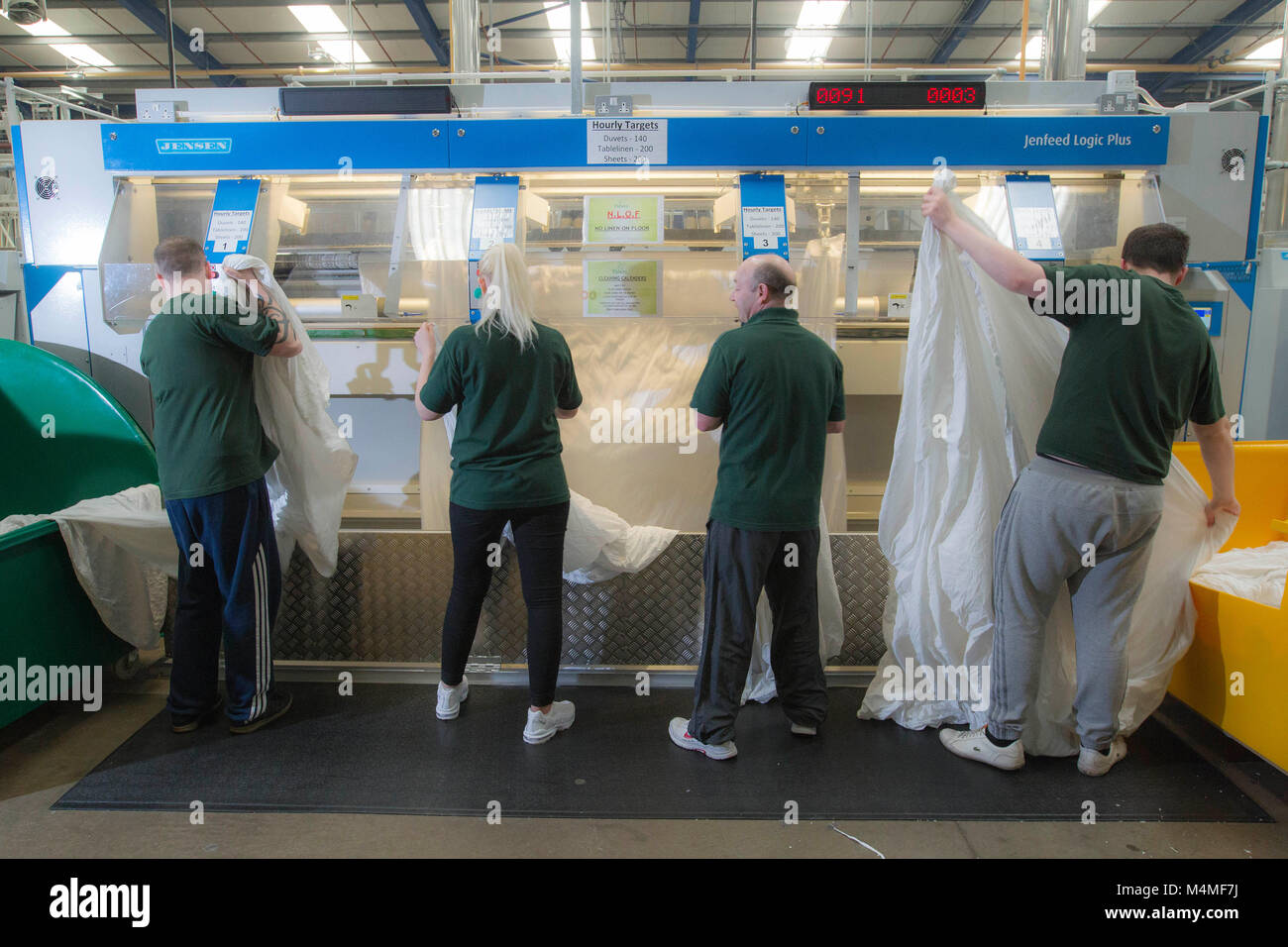 Factory workers working in industrial launderette - Stock Image