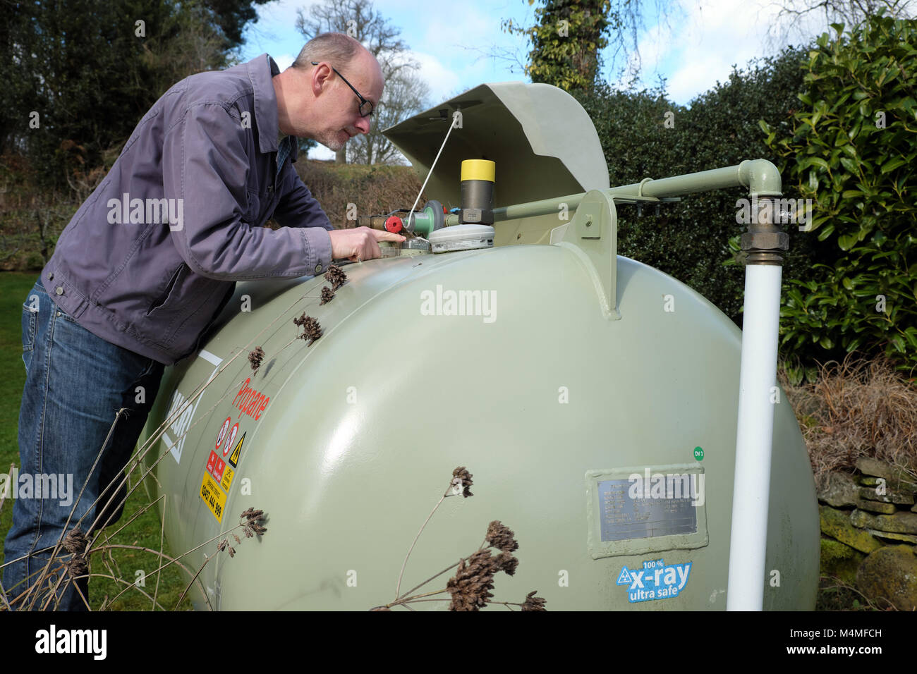 Calor gas male customer reading the capacity meter gauge in a rural UK setting - Stock Image