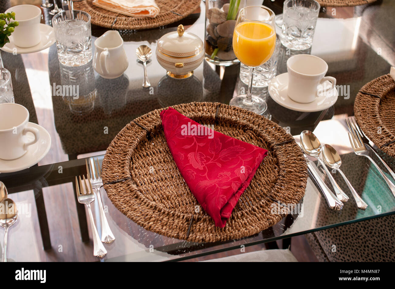 A glass table setting for brunch with glasses, cups, saucers, utensils, wicker placemats, and folded cloth napkin Stock Photo