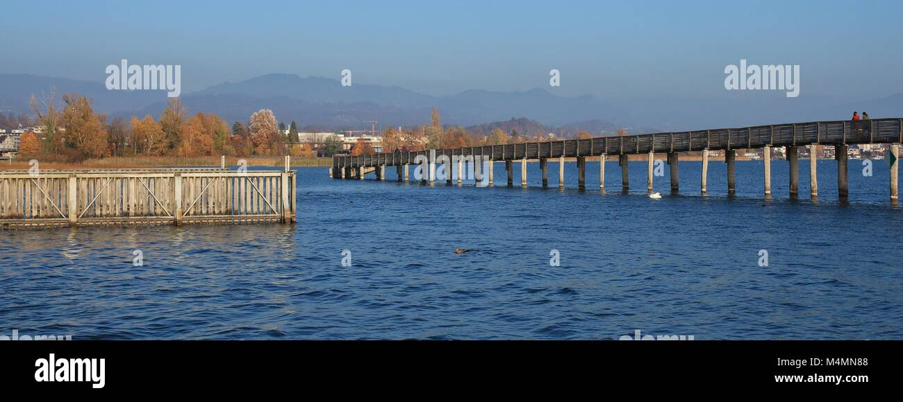 Boardwalk connecting Rapperswil and Hurden, Switzerland. Blue lake Obersee. - Stock Image