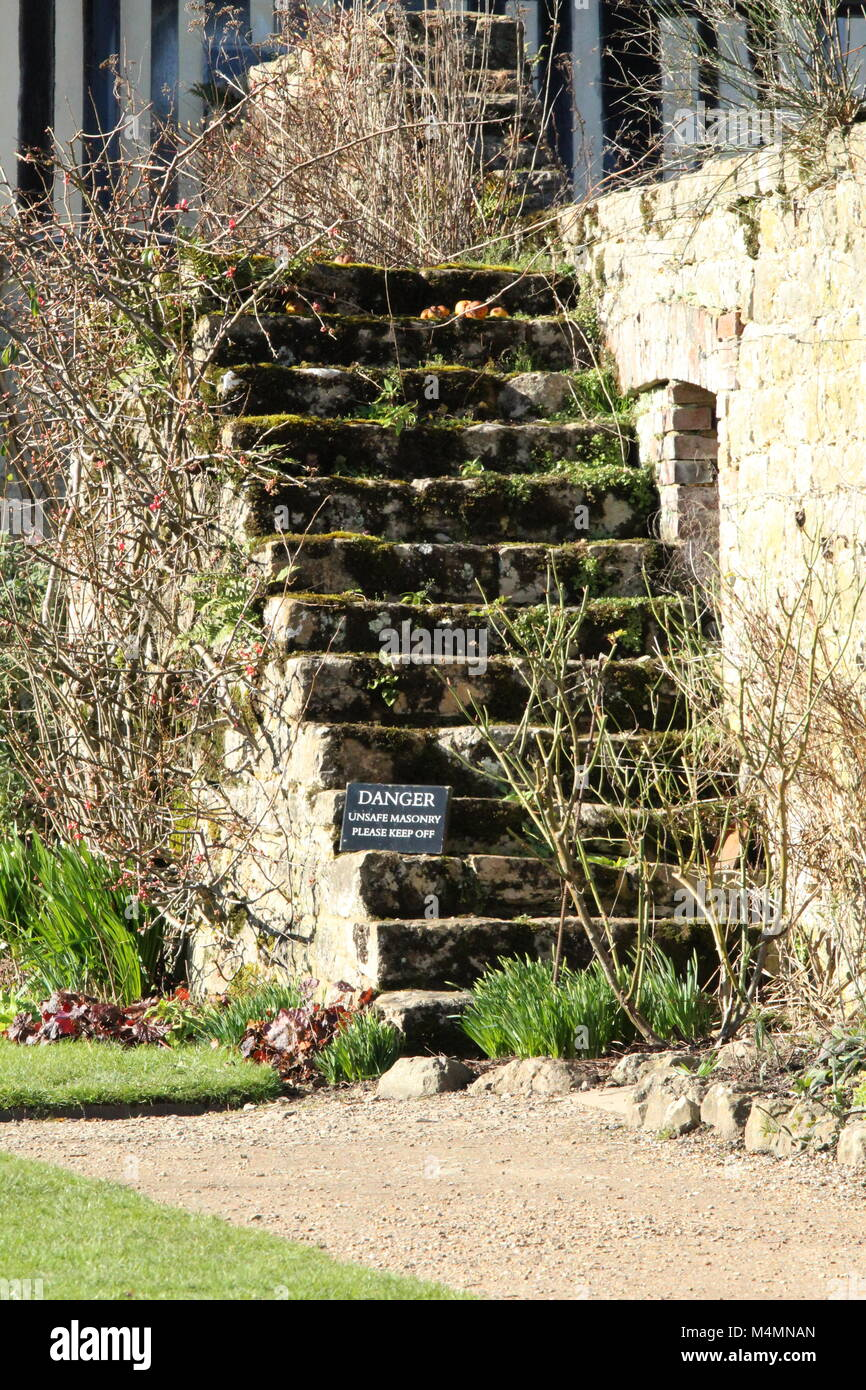 Ancient steps with danger sign do not climb in grounds of medieval manor house in Kent. - Stock Image