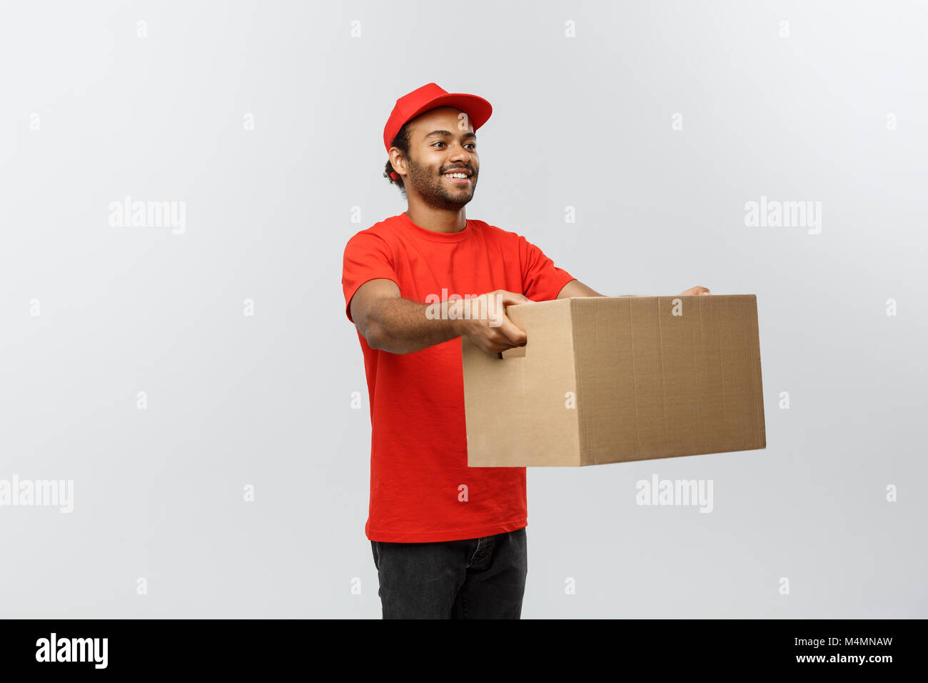 Delivery Concept - Portrait of Happy African American delivery man in red cloth holding a box package. Isolated Stock Photo
