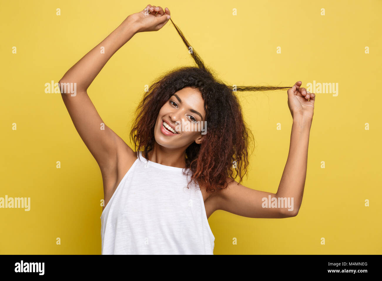 Beautiful attractive African American woman posting play with her curly afro hair. Yellow studio background. Copy - Stock Image