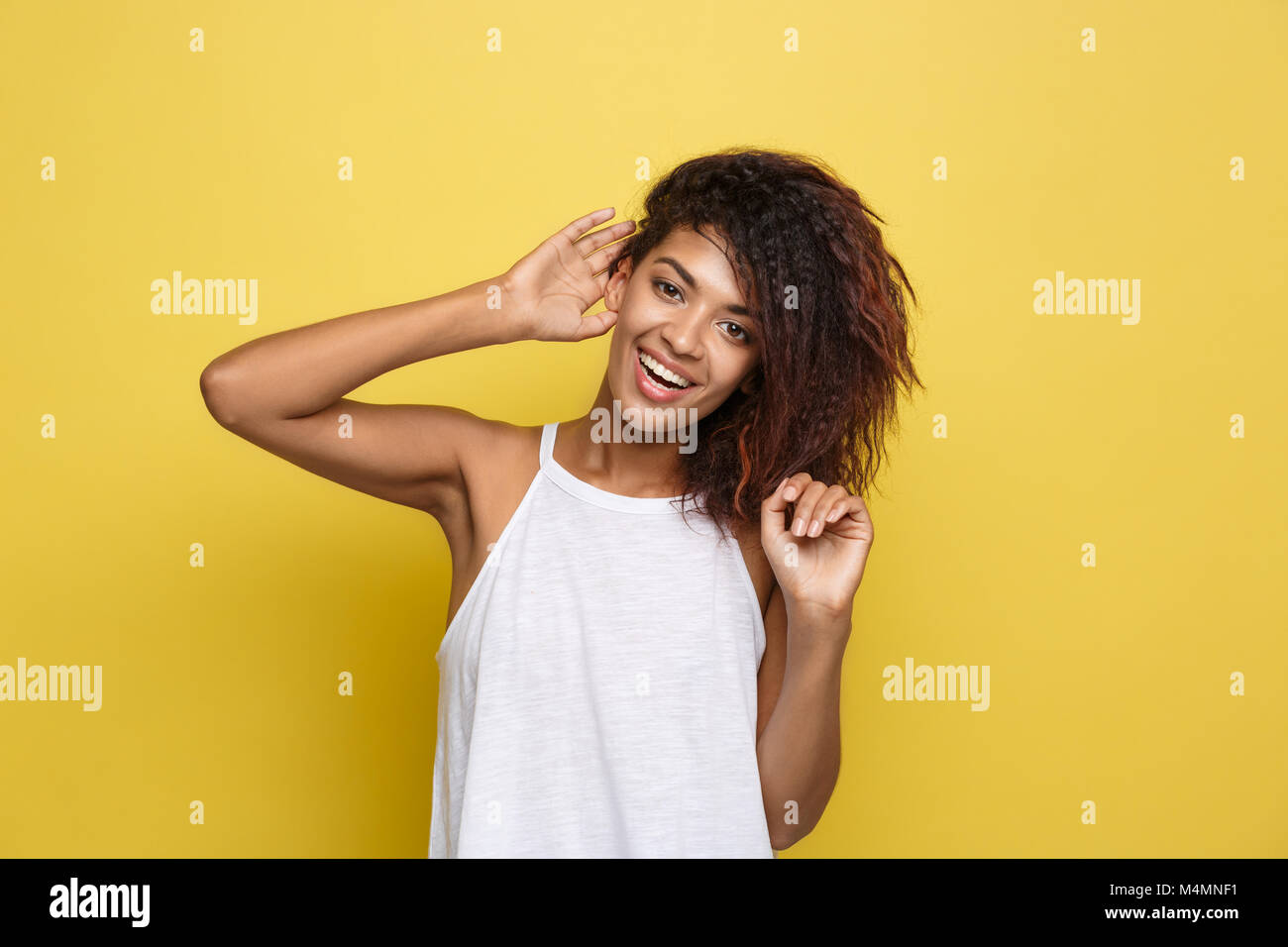 Beautiful attractive African American woman posting play with her curly afro hair. Yellow studio background. Copy Stock Photo
