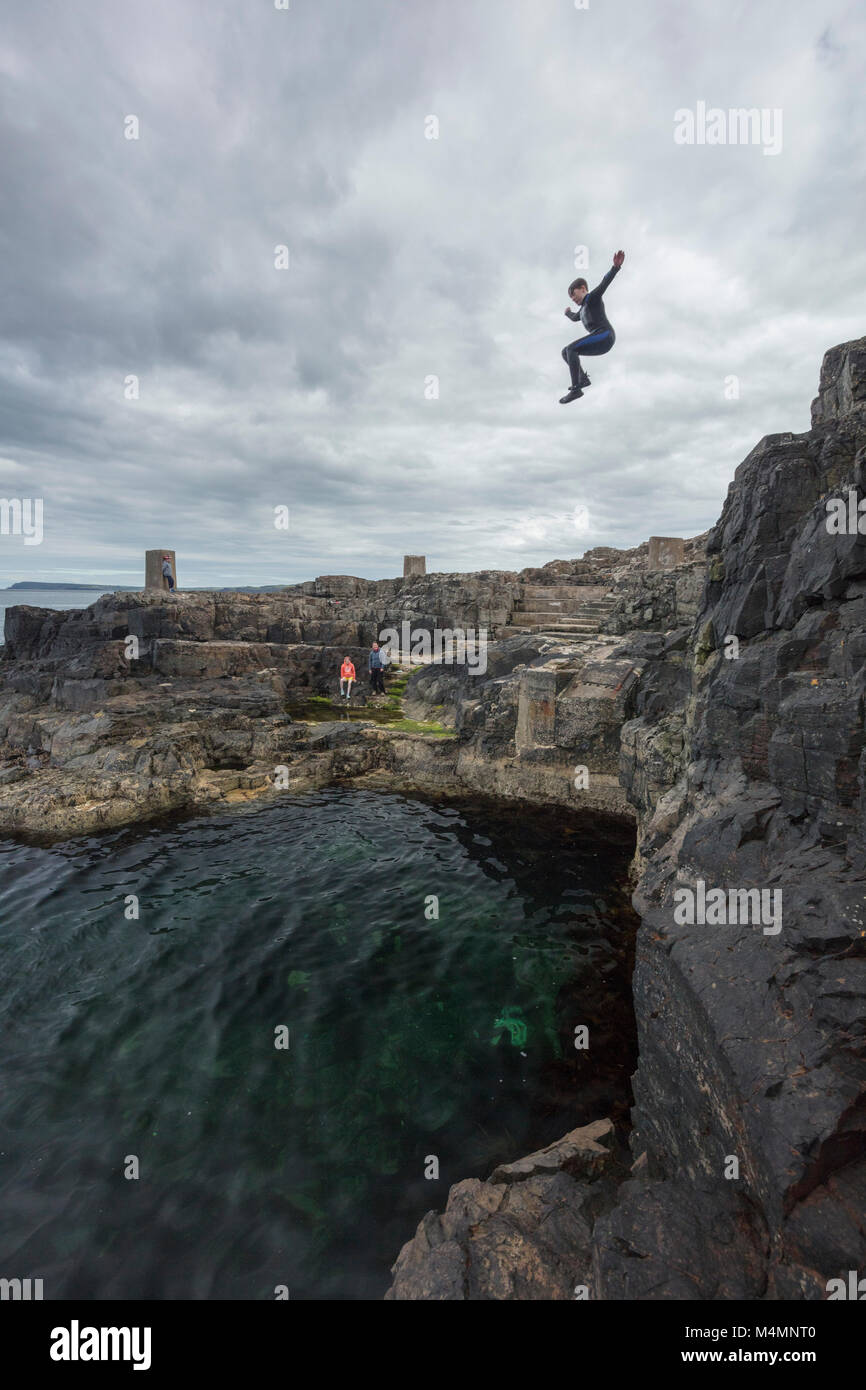 Cliff jumping into the Blue Pool, Portrush, County Antrim, Northern Ireland. - Stock Image