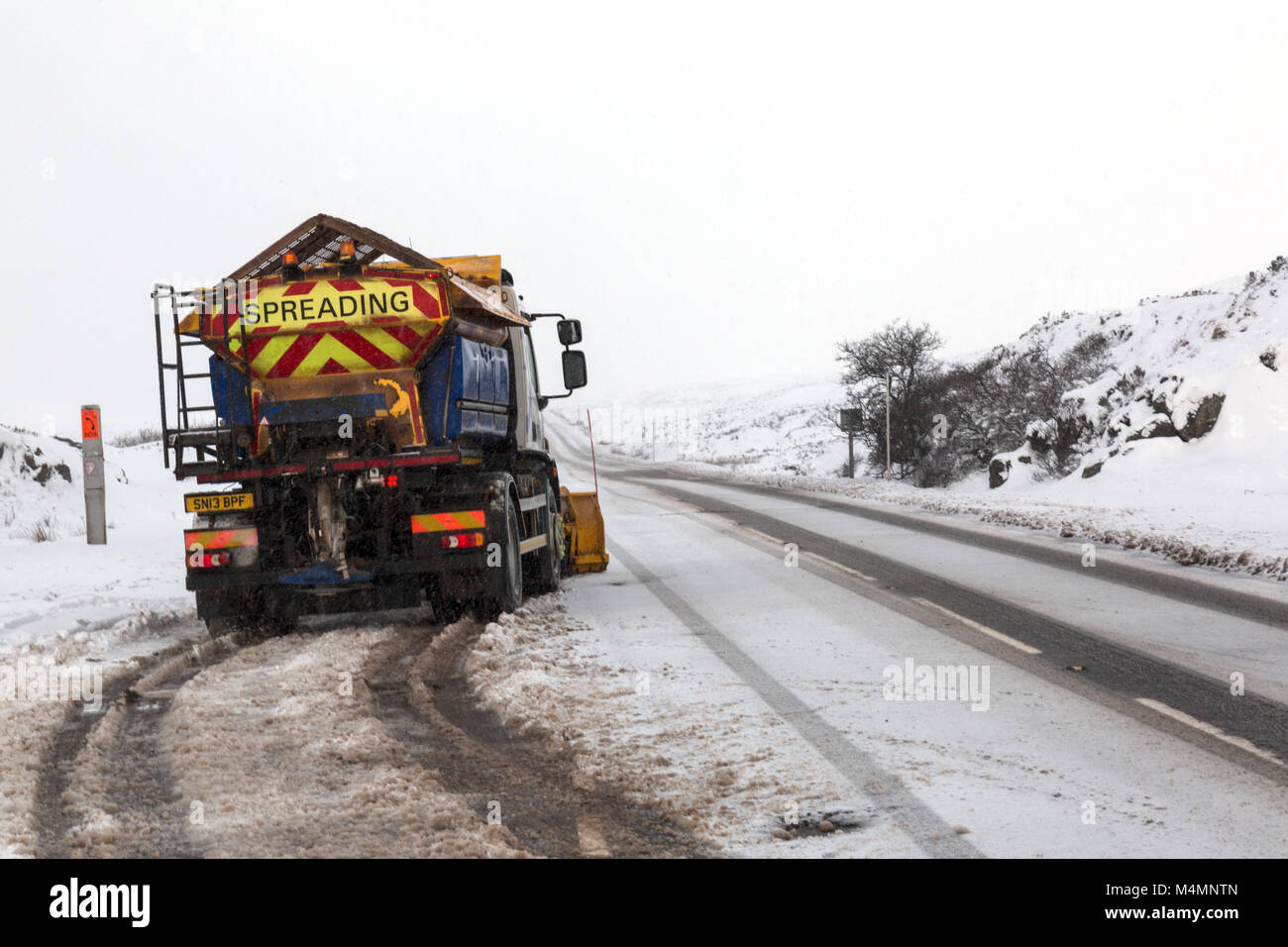 A salt spreading or gritting lorry by the side of  a raod with a dustin g of fresh snow in Glencoe, Scotland during - Stock Image