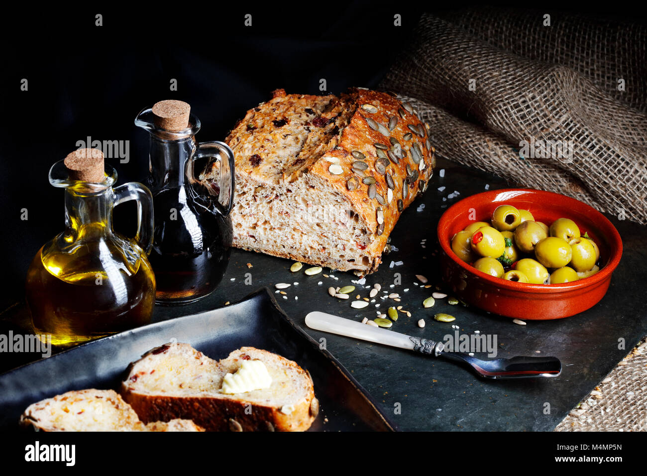 Fresh pumpkin seed bread with olive oil and butter Stock Photo