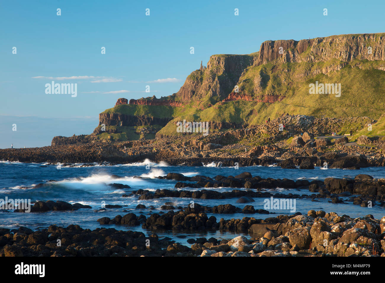 Lacada Point rises behind the Giant's Causeway, Country Antrim, Northern Ireland. - Stock Image