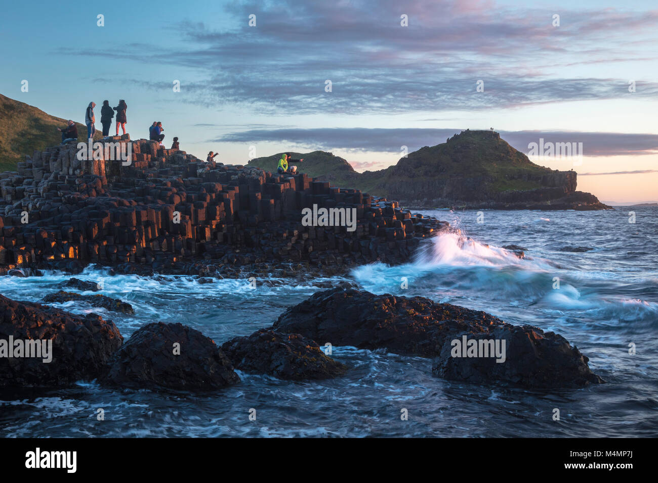 Evening visitors at the Giant's Causeway, Country Antrim, Northern Ireland. - Stock Image
