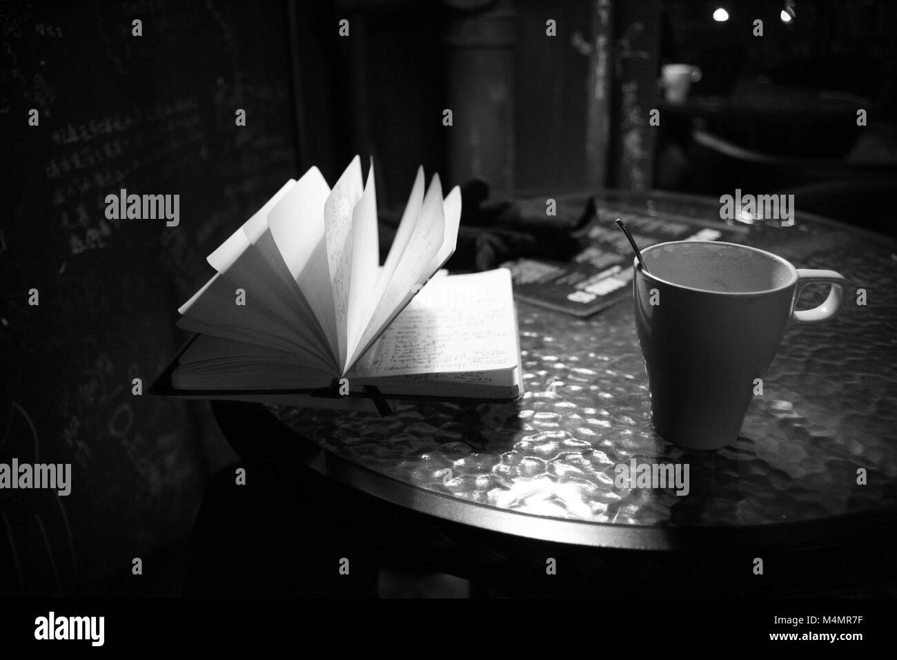 A notebook, a cup of cappuccino on a table at the Godot coffeeshop in Beijing - Stock Image
