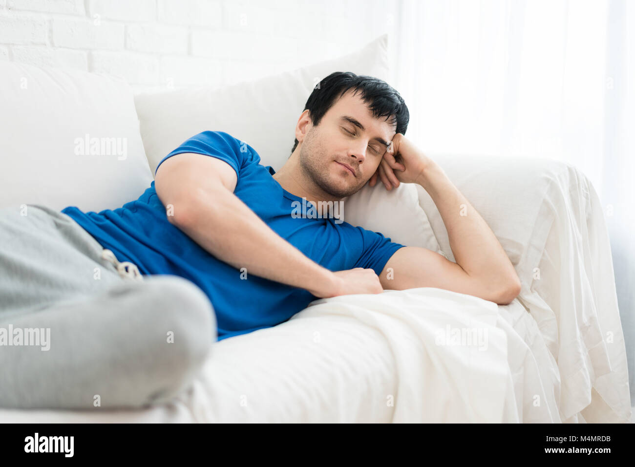 Time to relax. Handsome young man sleeping on the white sofa  at home. - Stock Image