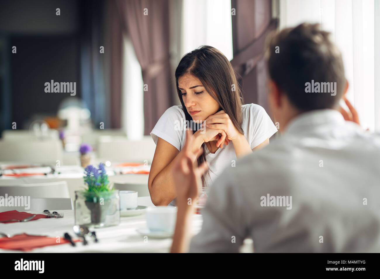 Sad depressed woman being verbally attacked.Mentally abused.Absent in conversation.Not listening.Private problems.Introvert - Stock Image