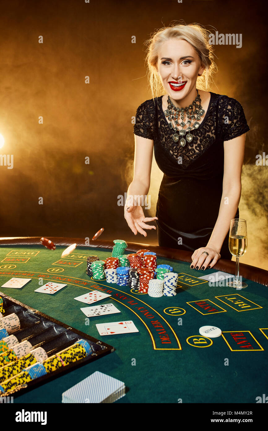 Young Woman In Evening Dress With Chips In Hand Standing Near Poker Stock Photo Alamy