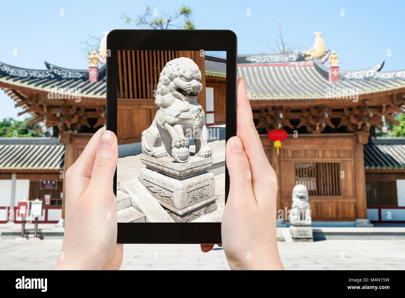 travel concept - tourist photographs lion statue near entrance to Guangxiao Buddhist Temple (Bright Obedience, Bright Stock Photo