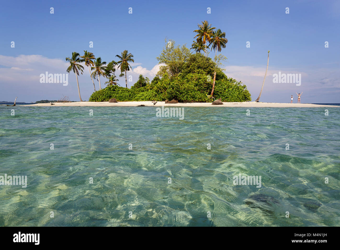 Woman and young boy standing on a sandy beach raising hands on a small tropical island on horizon in beautiful tropical - Stock Image