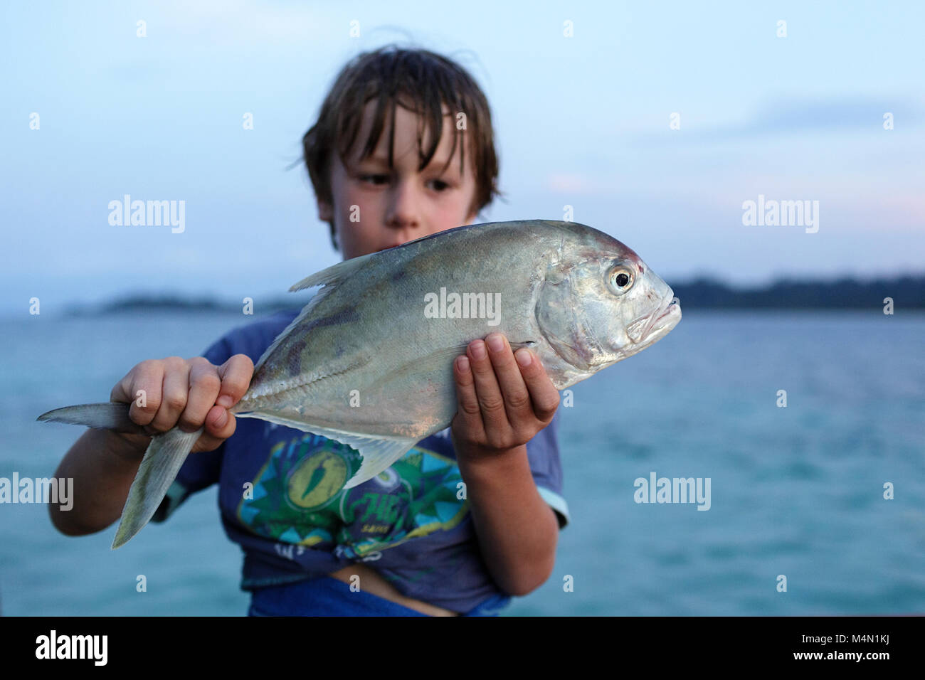 Happy face cute boy showing big fish he caught, portrait of preteen blonde child, summer travel and beach vacation - Stock Image