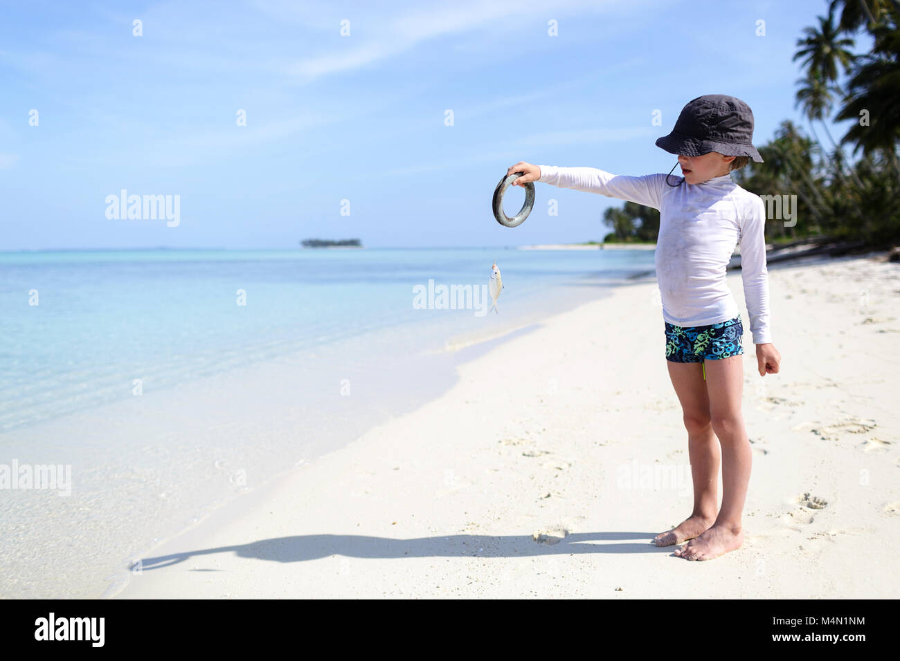 Happy face cute boy showing the fish he caught, portrait of preteen child with a hat, summer travel and beach vacation - Stock Image