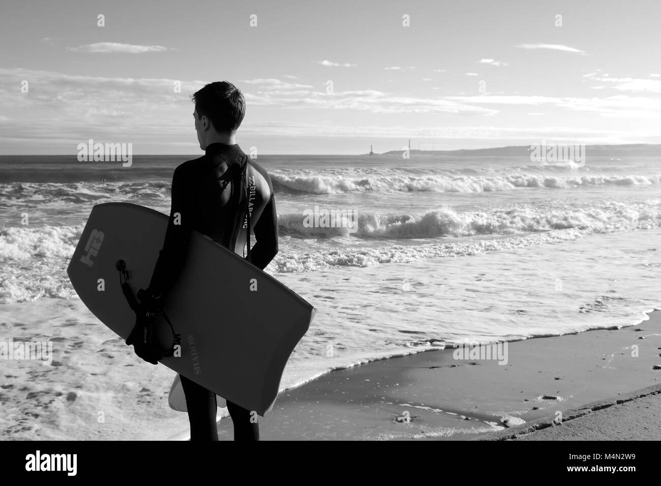 Male Bodyboarder Contemplating the Water before Surfing the Cold North Sea Waves at Aberdeen Beach, Scotland, UK. - Stock Image