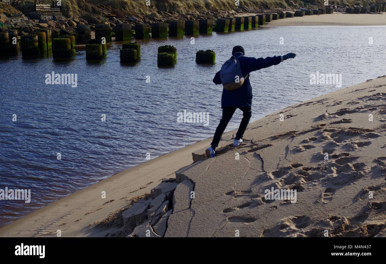 Young Man Collapsing the Sandy Bank of the Coastal River at Cruden Bay. Aberdeenshire, Scotland, UK. Stock Photo