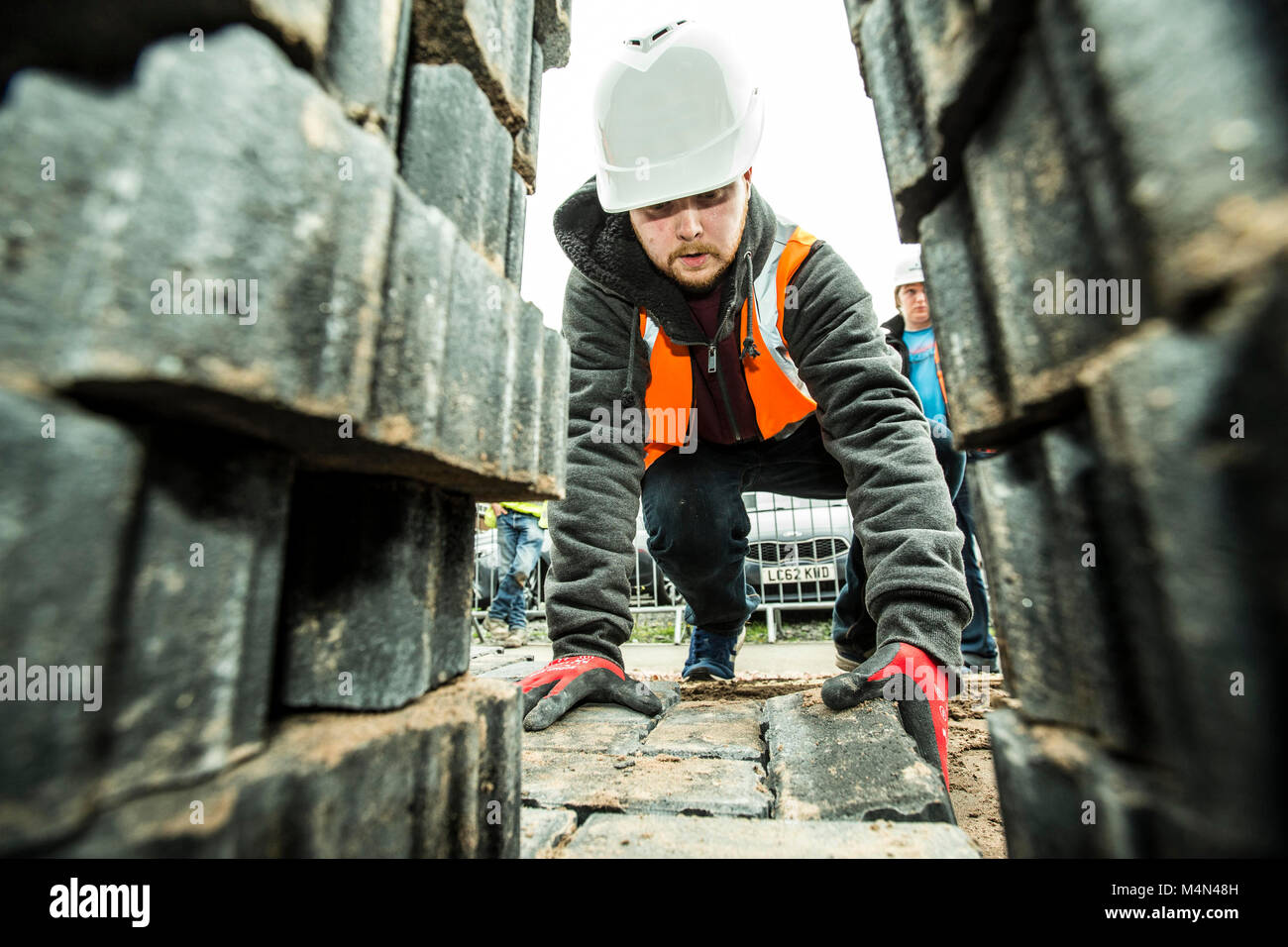 Apprentice learning how to lay bricks - Stock Image