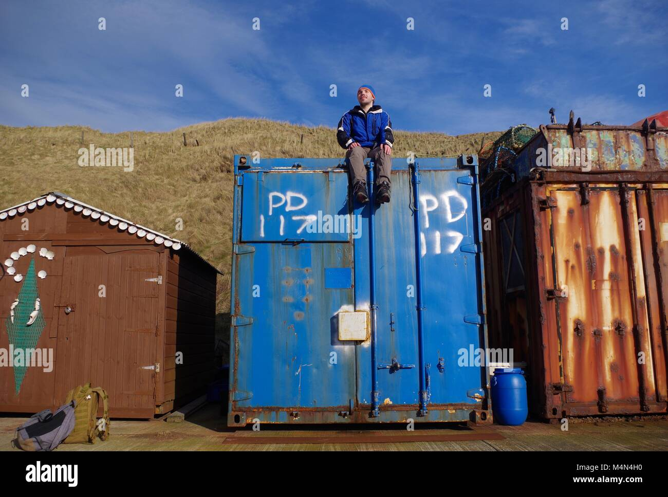Young British Man On Top of a Used Storage Shipping Container. Port Erroll, Cruden Bay, Aberdeenshire, Scotland, UK. North Sea Fishing Industry. Stock Photo
