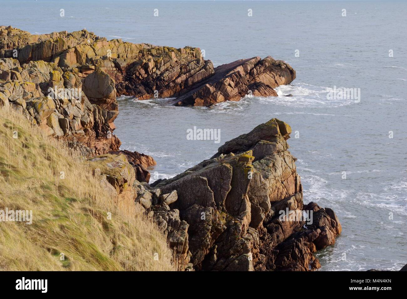Rugged Granite Cliffs of Cruden Bay Jutting Out into the Wild North Sea. Aberdeenshire, Scotland, UK. Stock Photo