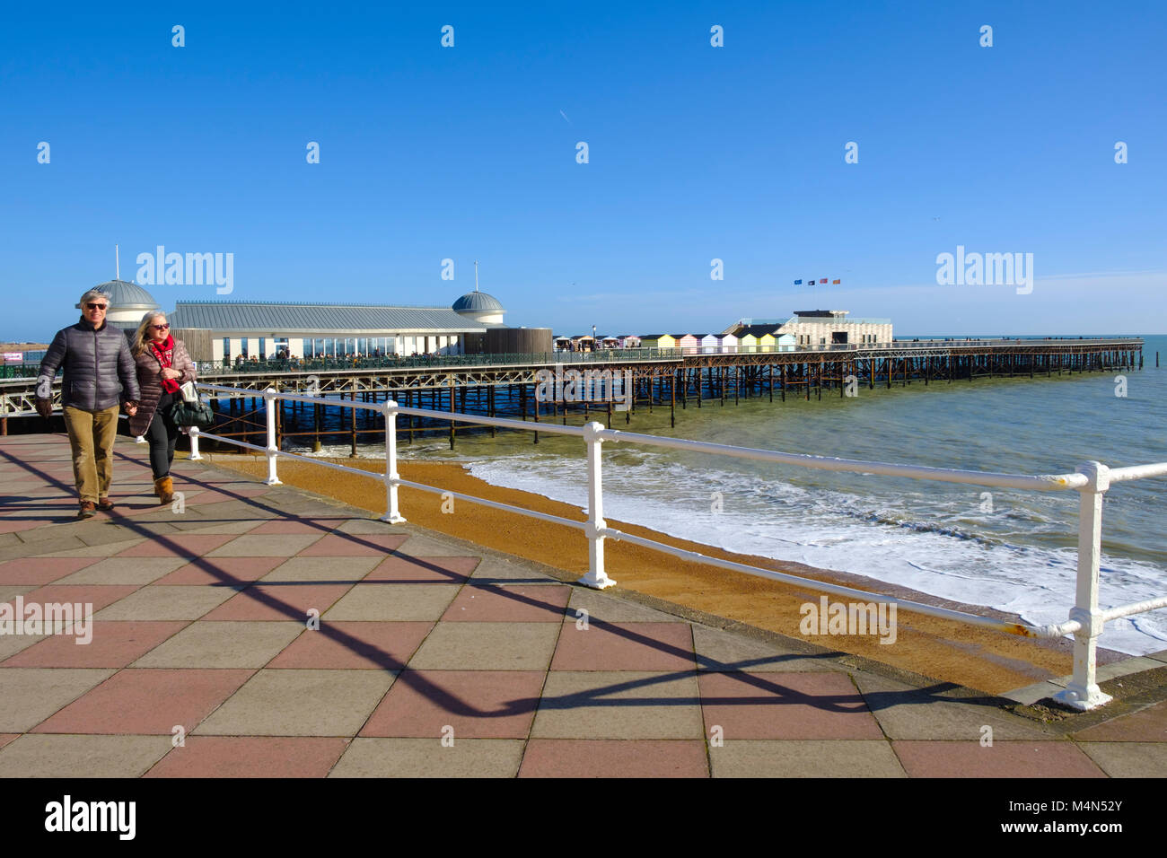 Hastings, East Sussex UK. A couple strolling along the promenade under a cloudless blue sky on a mild sunny day - Stock Image