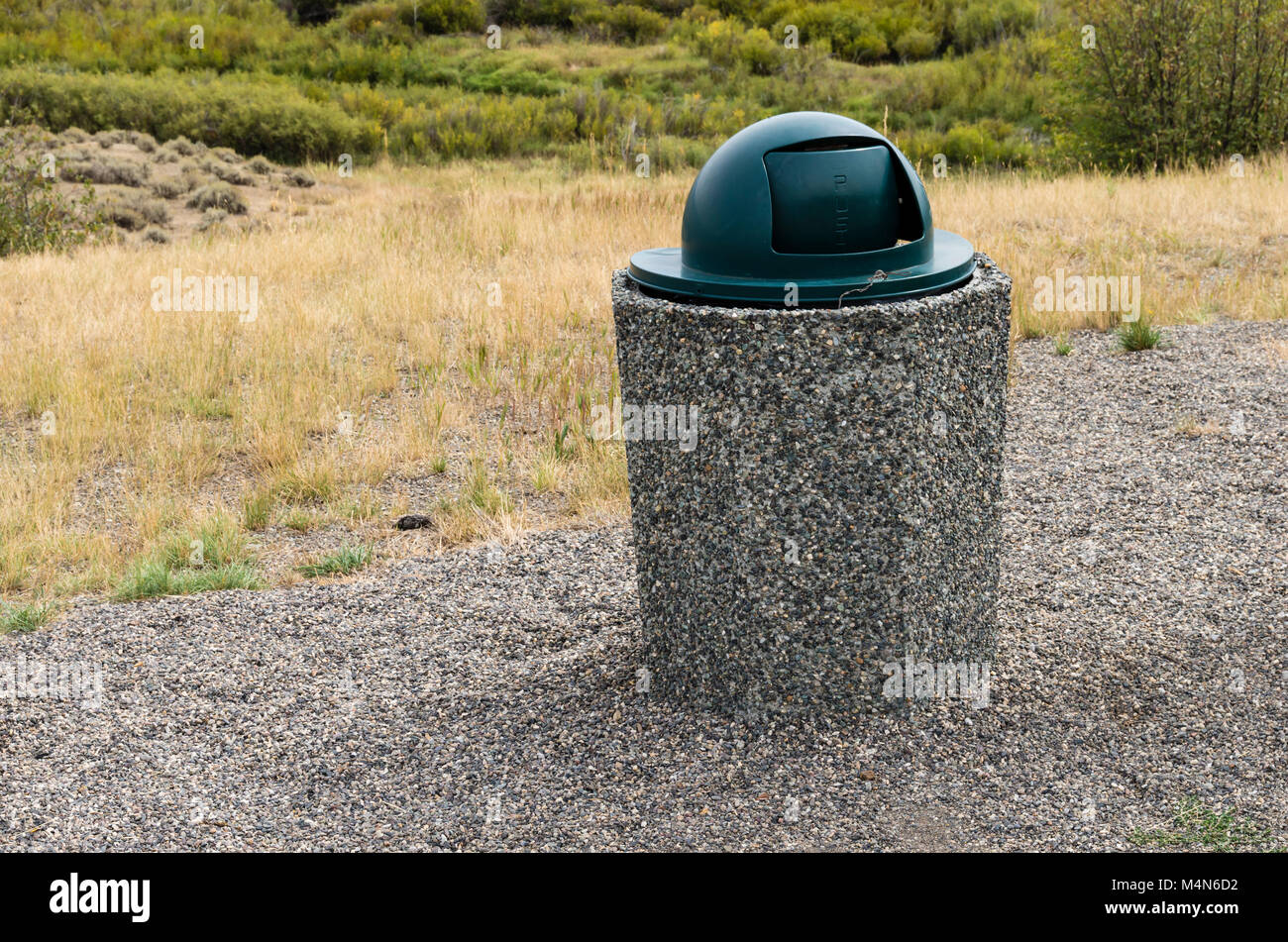 Covered trash can or garbage can at a rural roadside rest stop. - Stock Image