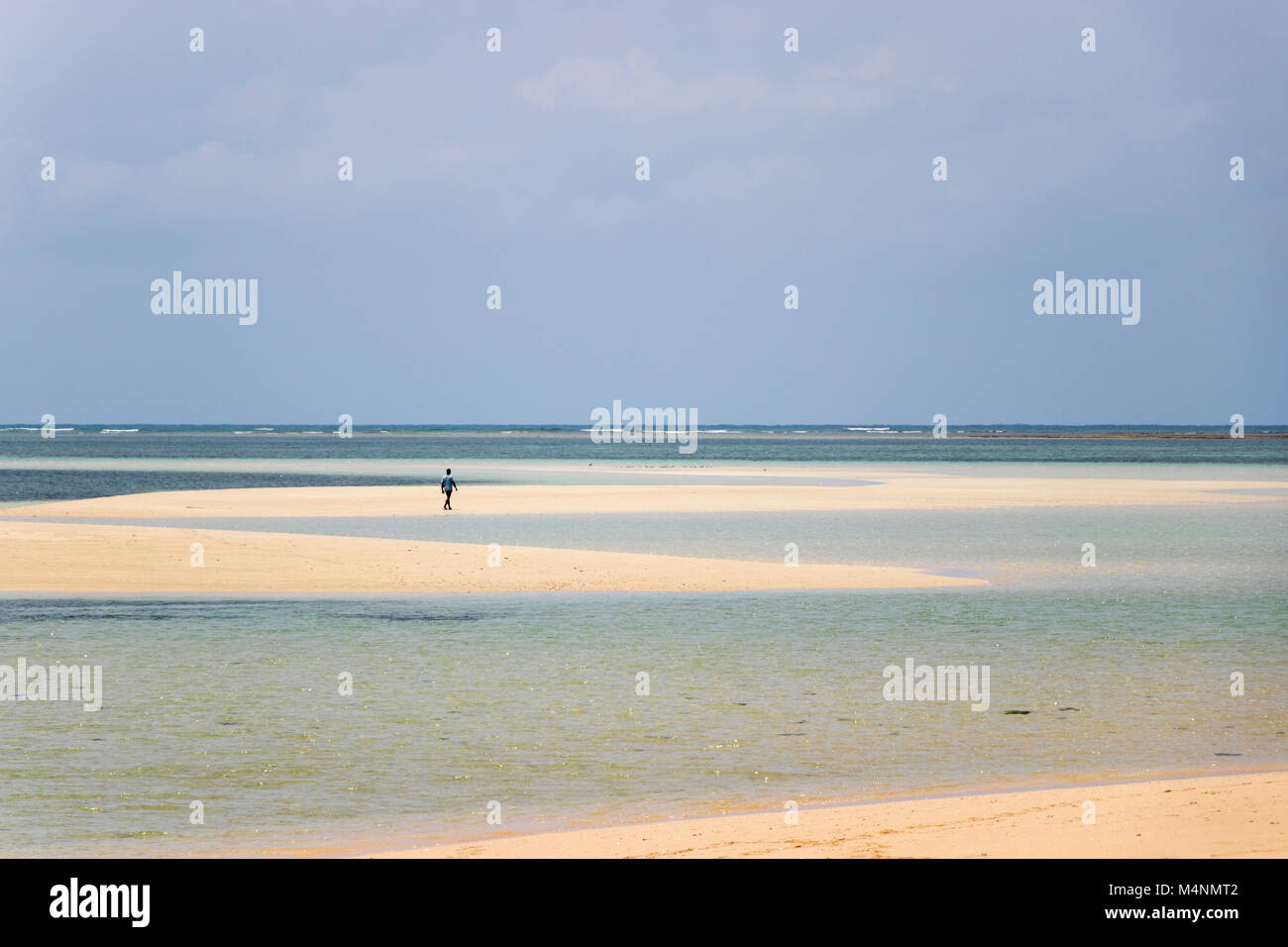Lone person walking desert island beach in Mozambique with turquoise sea - Stock Image