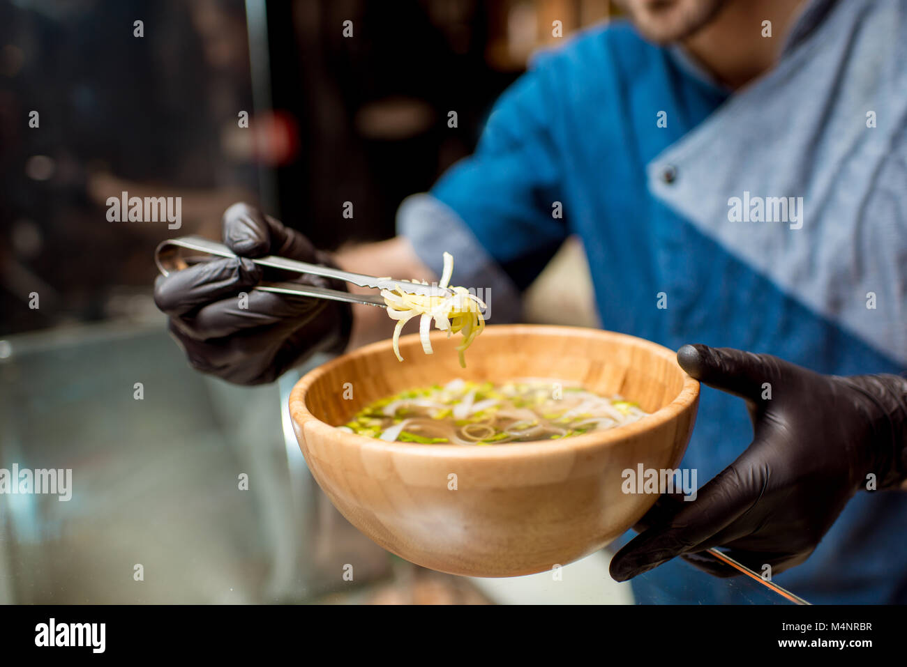 Chief cook decorating soup - Stock Image