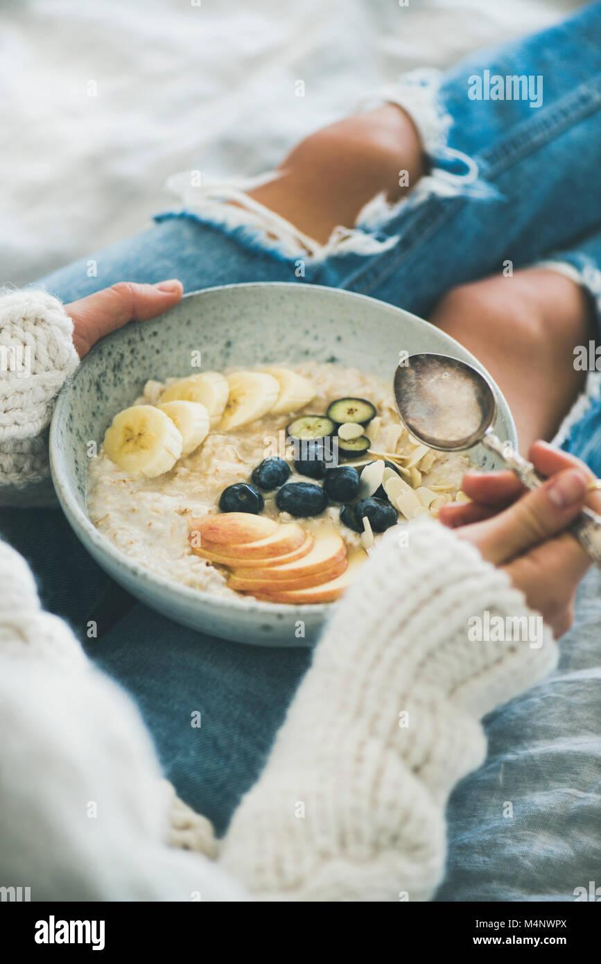 Healthy winter breakfast in bed. Woman in woolen sweater and shabby jeans eating vegan almond milk oatmeal porridge - Stock Image
