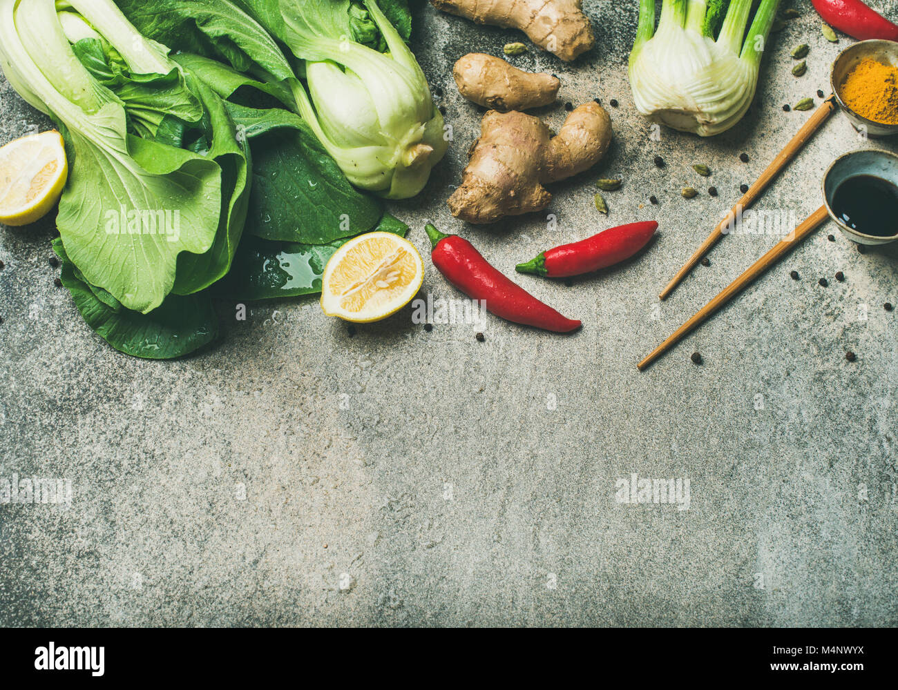 Asian cuisine ingredients over concrete background, top view, copy sapce. Flat-lay of vegetables, spices and sauces - Stock Image