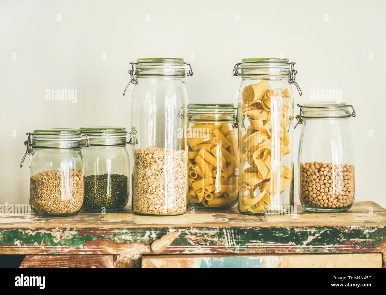 Various uncooked cereals, grains, beans and pasta for healthy cooking in glass jars on rustic table, white background, - Stock Image