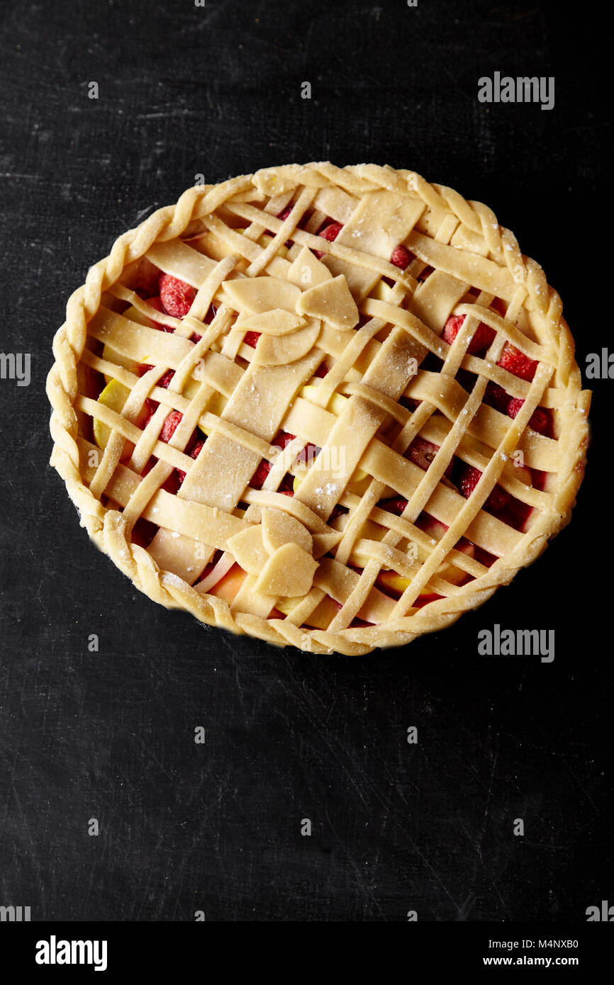 Pie crust design ideas - various ways of pie decoration with lattice and leaves. Apple, strawberry and raspberry - Stock Image