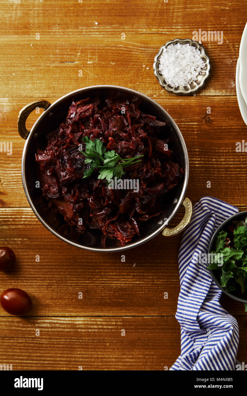 Vertical image of red cabbage with beetroot braised in red wine sauce served with sea salt and parsley. Vegetarian - Stock Image
