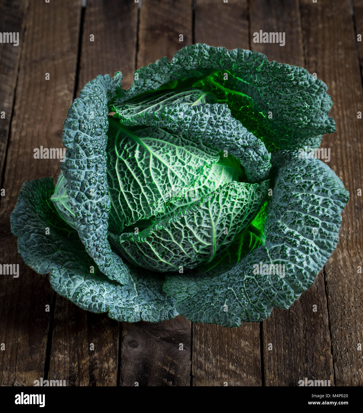 fresh savoy cabbage closeup on rustic wooden background - Stock Image